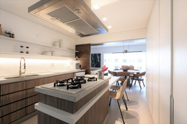 The kitchen shows off wooden cabinets and white stone countertops, with built-in lights and sliding panels that can be opened or closed
