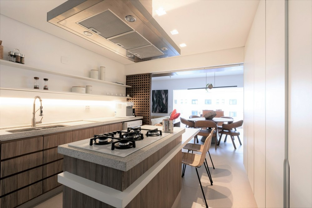 The kitchen shows off wooden cabinets and white stone countertops, with built in lights and sliding panels that can be opened or closed