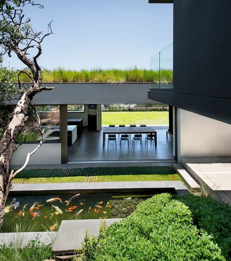 The living areas can be opened to outdoors, and there you can see a green lawn and a pond with real fish