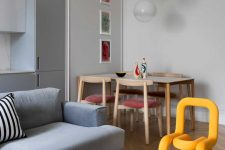 04 The dining space is done with a wooden table, pink chairs and bold artworks and pendant lamps