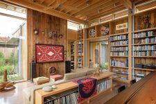 04 The living room is done with open shelving, a large sectional, bright boho art and accessories