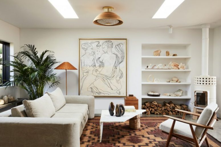 The living room is stylish and calming, with a bold artwork and a statement plant