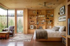 05 The bedroom has several glazed walls and is all done of wood and plywood plus boho textiles