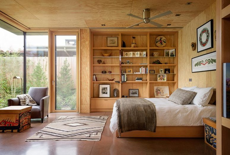 The bedroom has several glazed walls and is all done of wood and plywood plus boho textiles