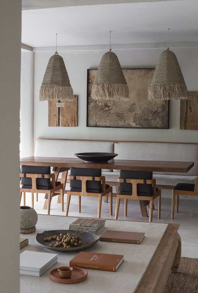 The dining space is done with comofrtable chairs, woven pendant lamps and pieces of the house hung as a gallery wall