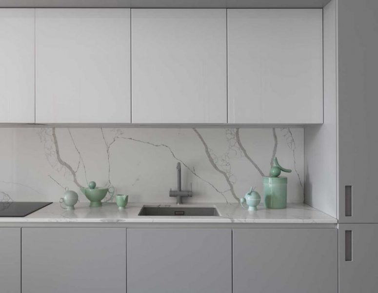 The kitchen is done in two shades of grey, with a marble backsplash and countertops