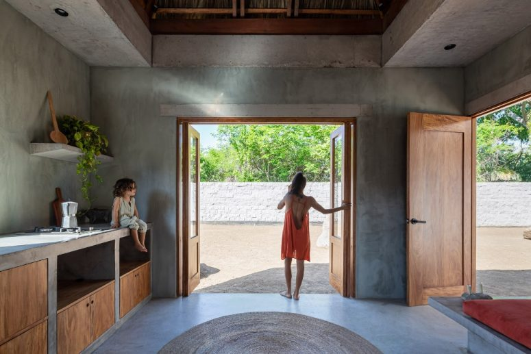 The kitchen is done of concrete, with plywood cabinets and it fully opens to outside