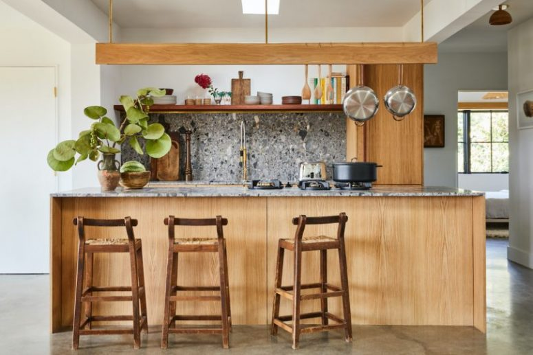 The kitchen is done with light-colored cabinets and grey terrazzo surfaces plus a hanging shelf over the kitchen