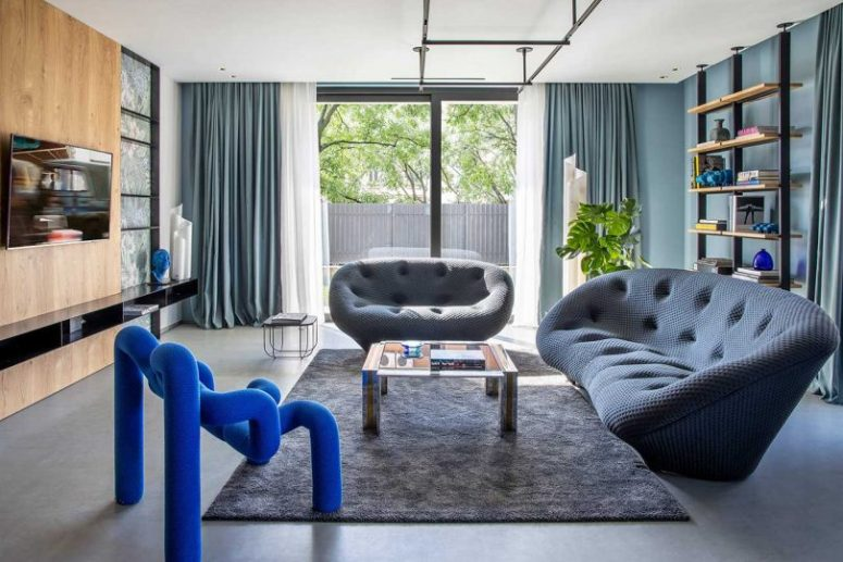 The living room is done with slate grey sofas, an industrial shelf and a gorgeous electric blue chair that steals the show