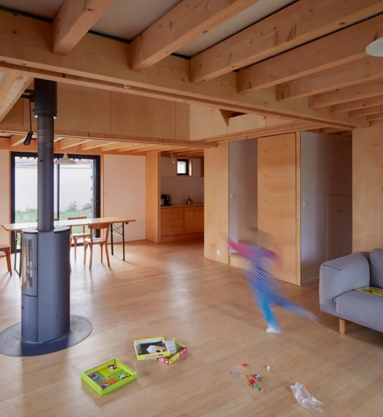 The main layout comprises a kitchen, dining and living room, it's fully clad with light-colored plywood and features a hearth in the center