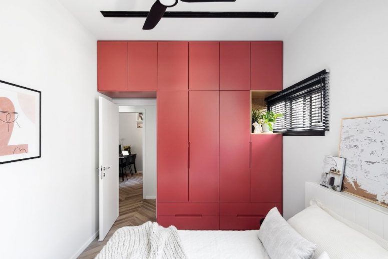 This red accent is a sleek storage unit that takes a whole wall