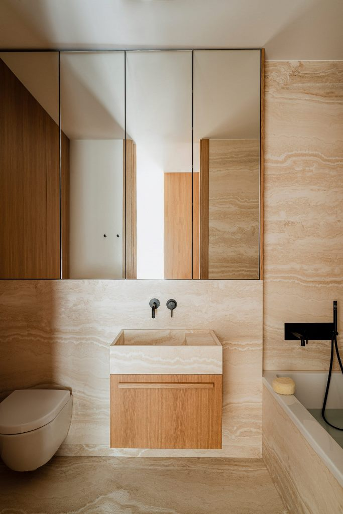 The bathroom is also clad with travertine marble, and there's an oak vanity to echo with the kitchen