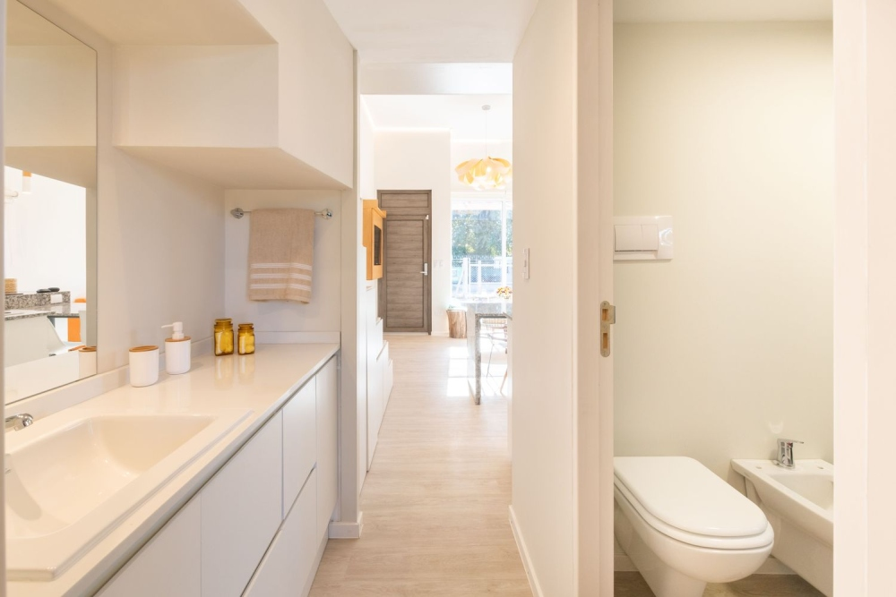 The bathroom is very small and sleek and is done in light colors to make it feel spacious and airy