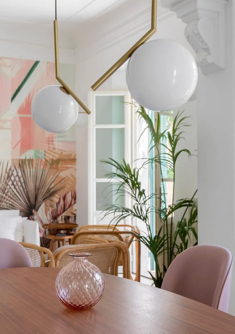 The dining space is done with an oval table, pink chairs, a pink vase and catchy pendant lamps