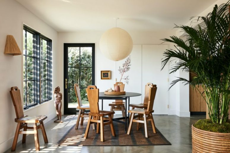 The dining space is maked with a geometric table and vintage wooden chairs
