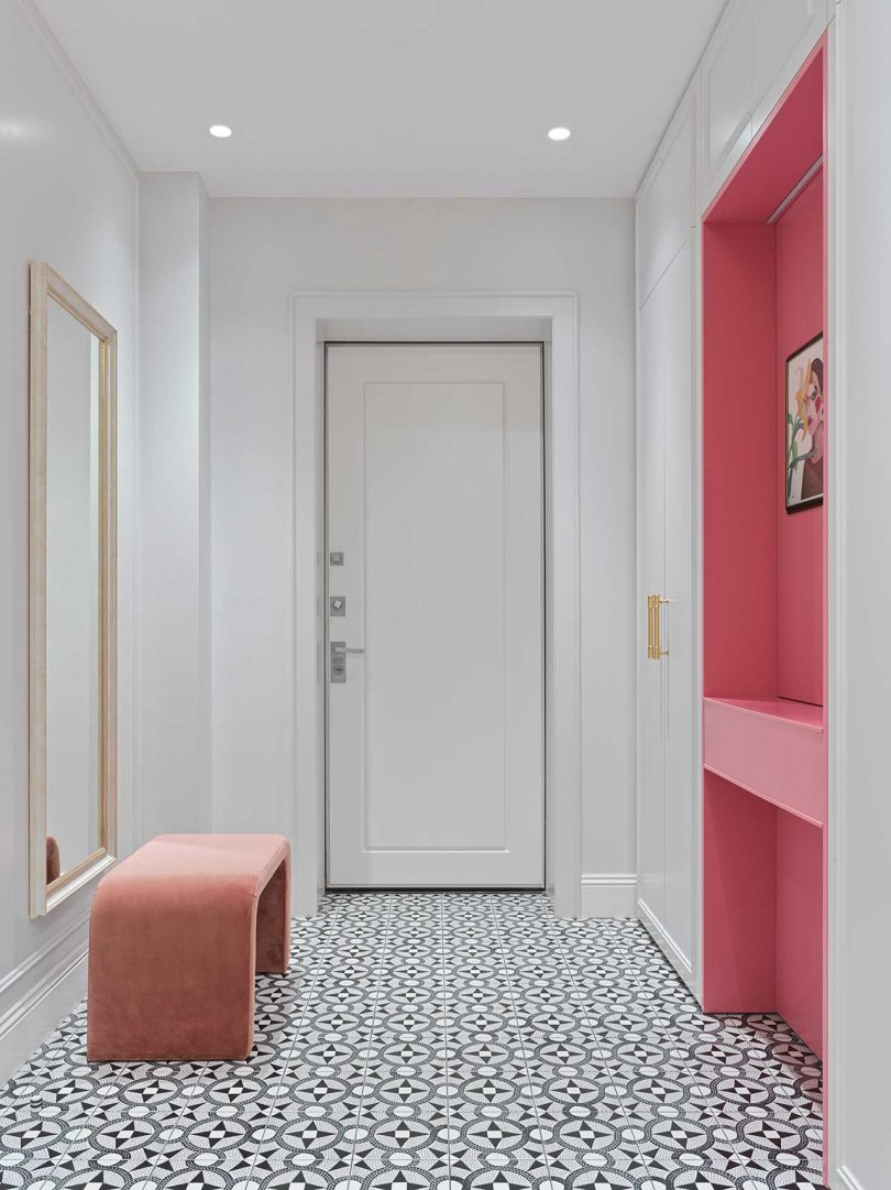The entryway shows off a pink vanity, a pink bench, a mirror and hidden storage and black and white tiles