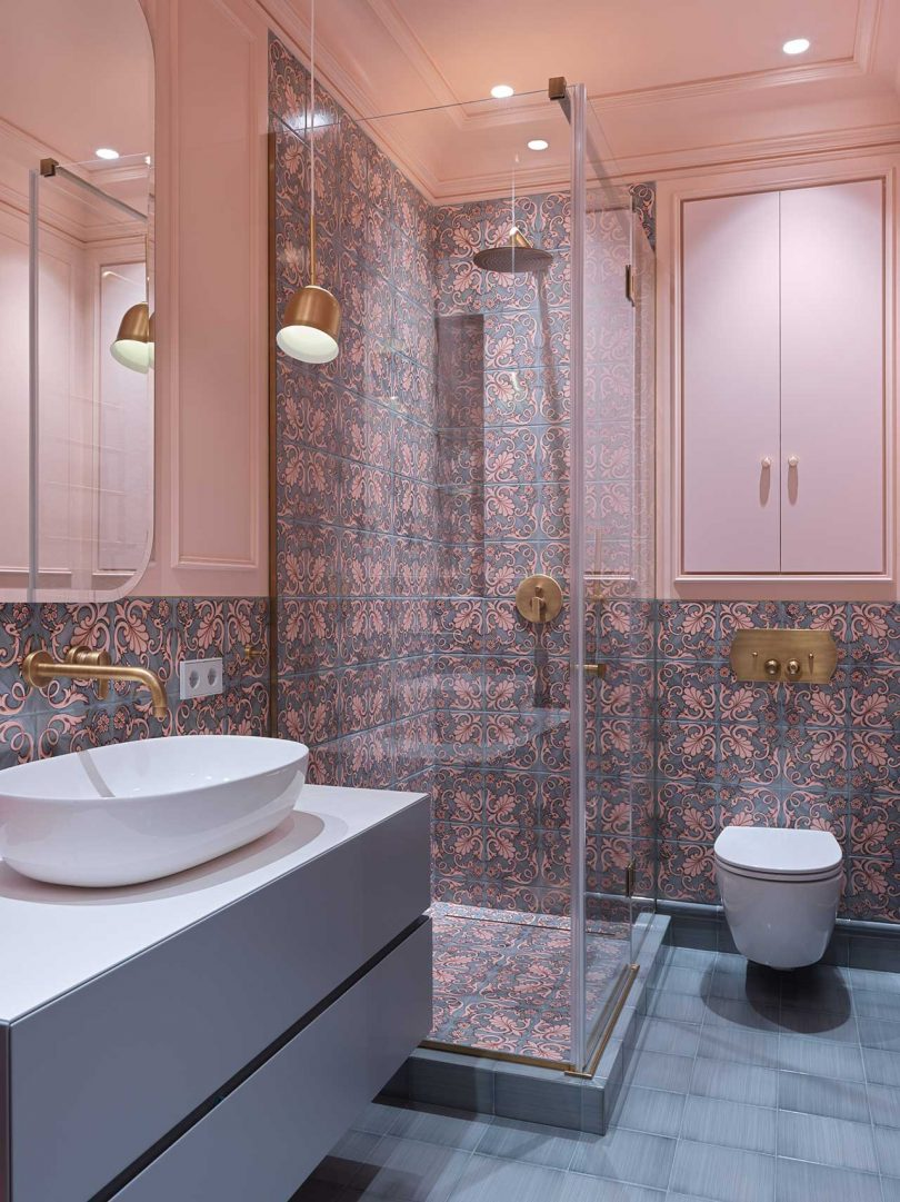 The bathroom is clad with bright patterned and grey ones on the floor and pendant lamps