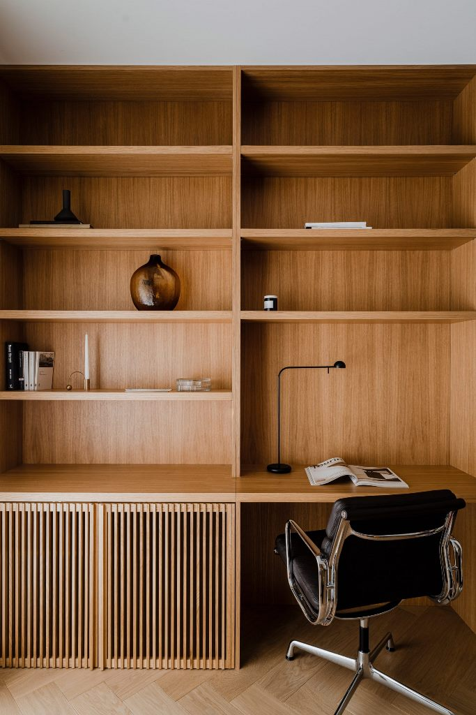 The home office is done with wood, there are open and closed storage units and a stunning black chair
