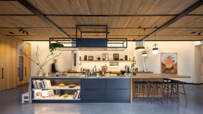 The kitchen is done with dark metal cabinets, there's a small wooden breakfast bar, with many lights and wooden stools