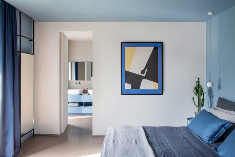 The bedroom features some cool furniture, navy and grey bedding and bold art