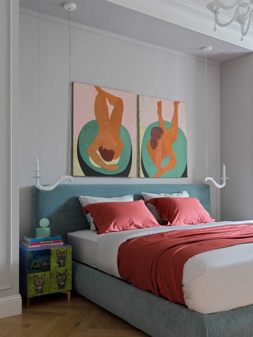 The bedroom shows off a grey upholstered bed, colorful nightstands and bold artworks