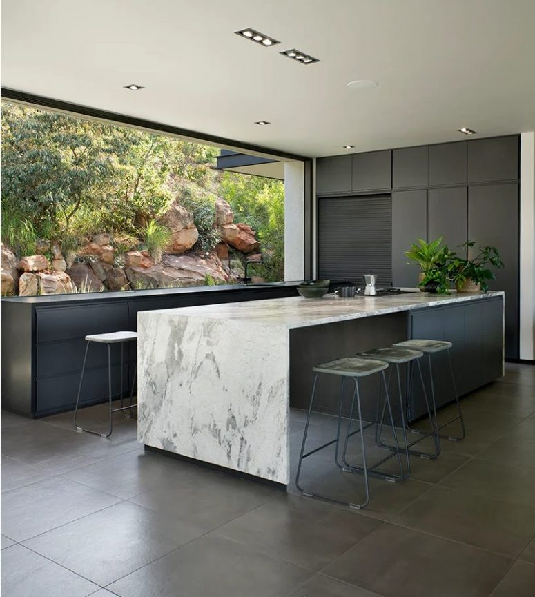 The kitchen is done with graphite grey cabinets, a large kitchen island with a white marble countertop