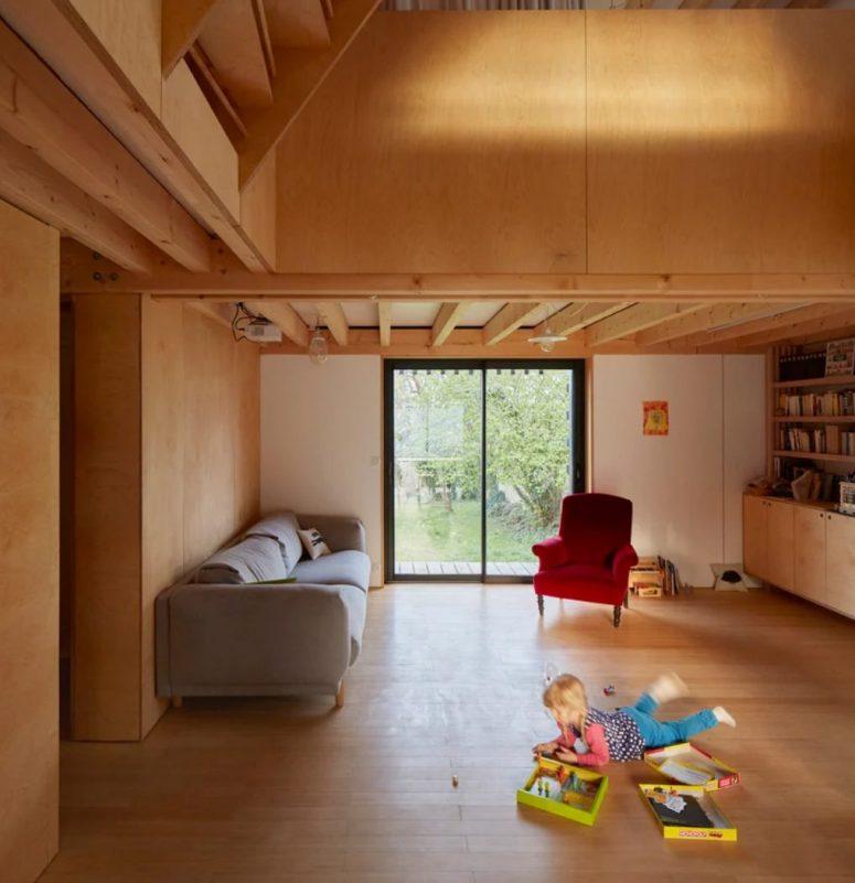 The living room shows off a lot of books, too, there's a modern sofa and a vintage chair, it's a large play space for the kid