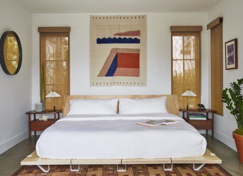 The master bedroom is done with bold touches, comfortable mid century modern furniture and burlap shades