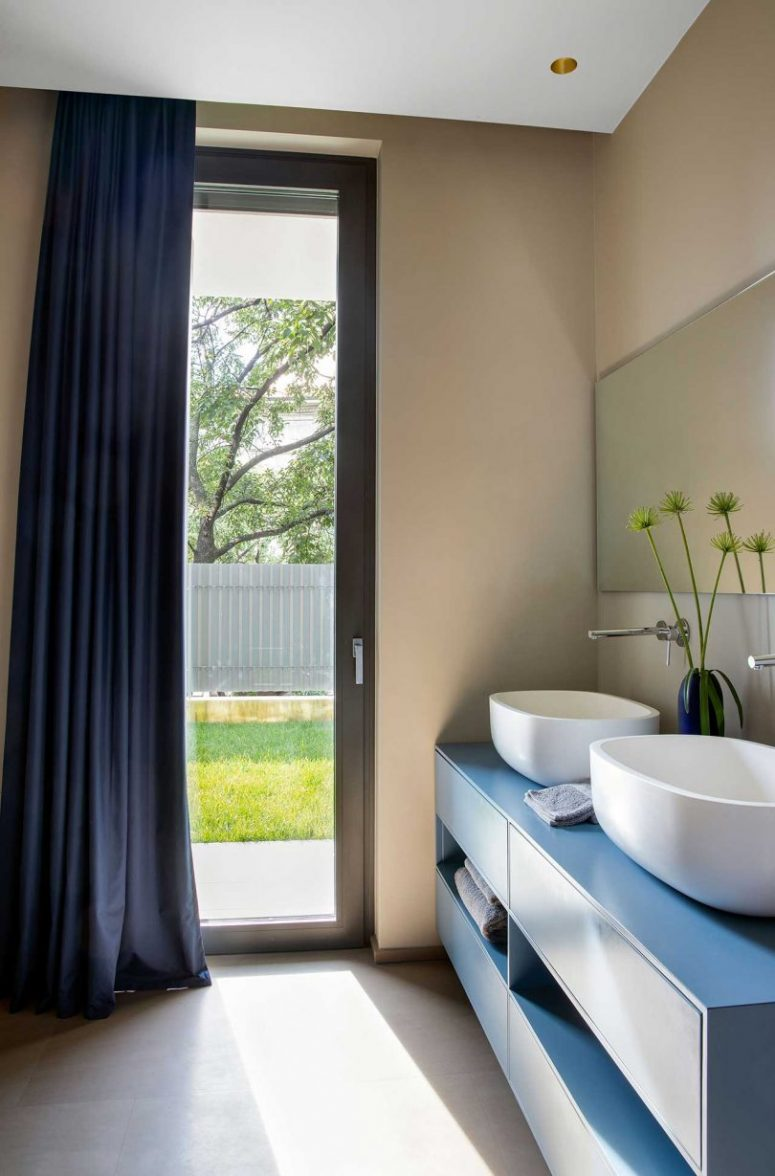 The bathroom is done with a blue double vanity, a navy curtain may be used for privacy