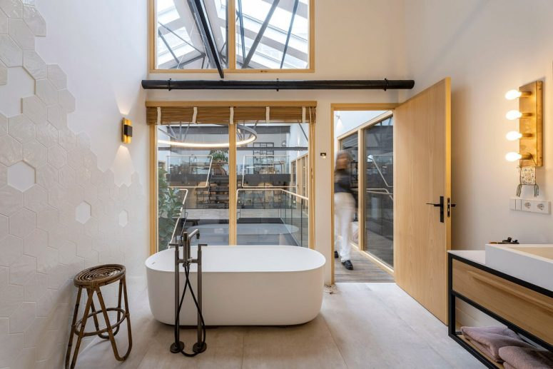 The bathroom is simple and minimalist, with large windows, an oval tub and a large vanity