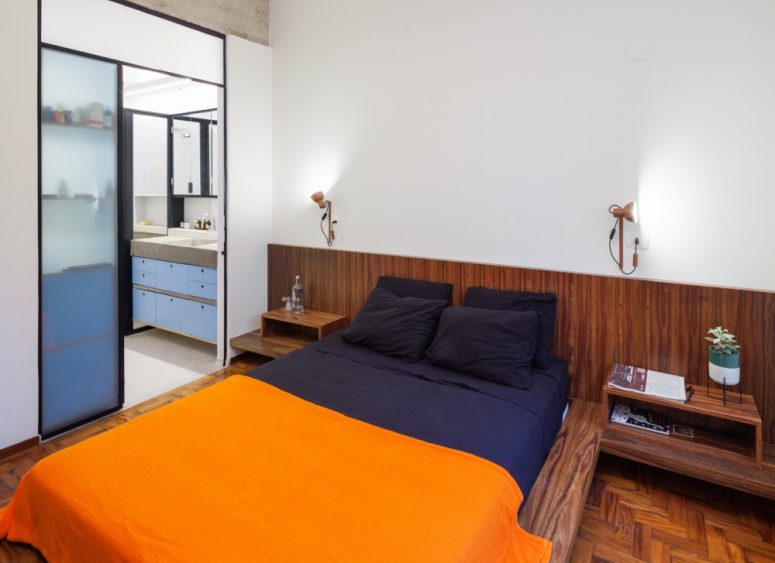 The master bedroom shows off darker wooden furniture and parquet floors, sliding doors lead to a grey and blue bathroom