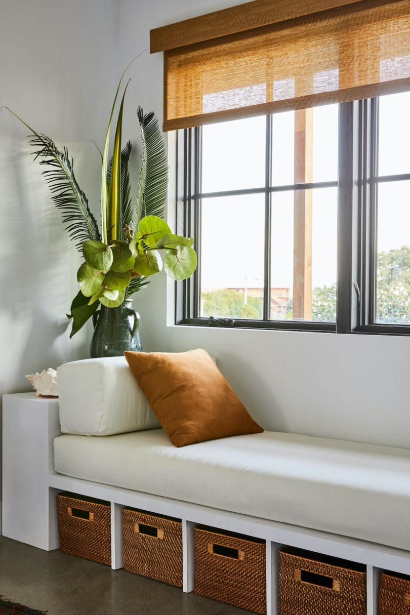 There's a window daybed with storage unit it that is also accented with a statement plant arrangement