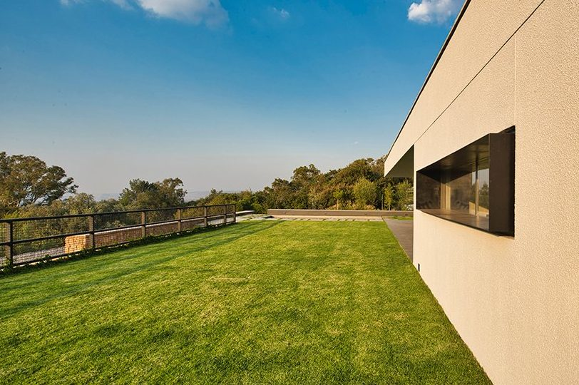 The living room lawn terrace is positioned on top of the service level, buried below the landscape