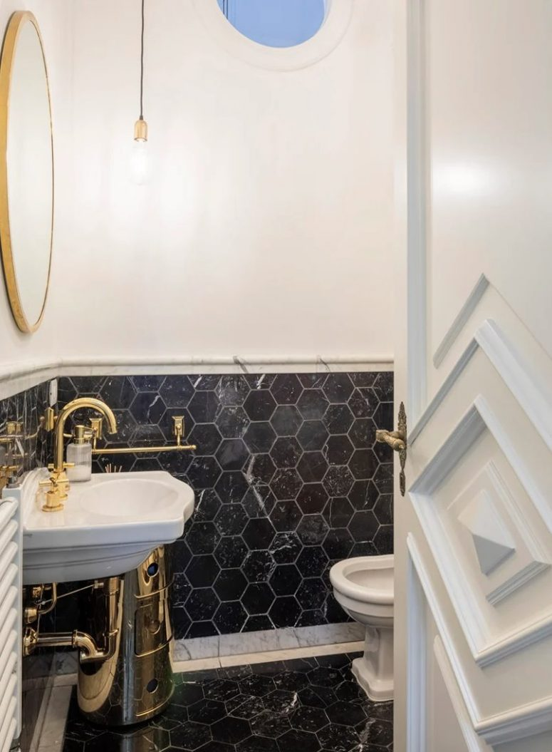 The bathroom is clad with black marble tiles, there are some gold touches that echo with apartment