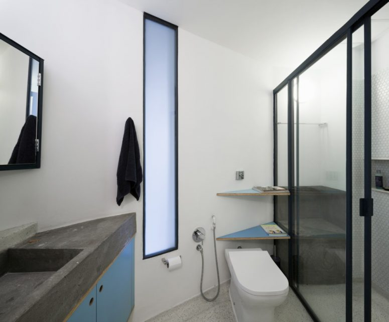 The bathroom is small, done in grey, white and blue with concrete countertops and a comfy shower