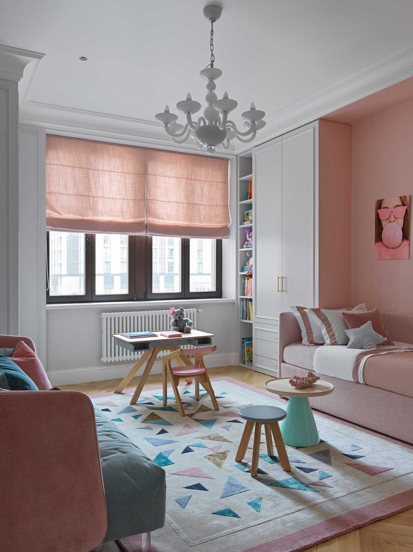 The kid's room is done with blush and pink furniture, blush curtains, a geometric rug and catchy tables