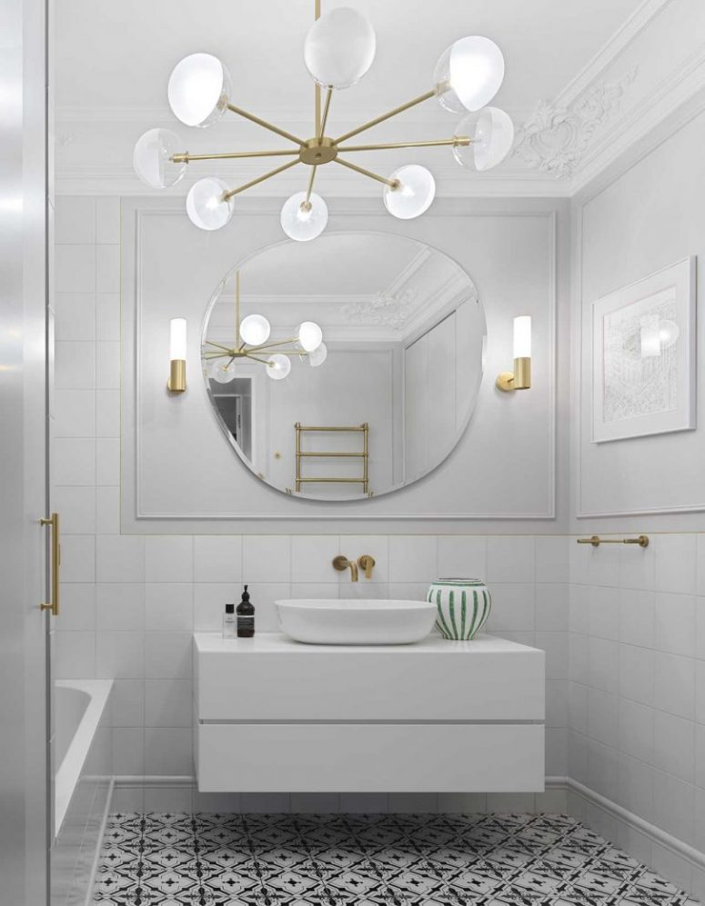 Another bathroom is done in white, with a black and white patterned floor, chic and elegant lamps and brass touches