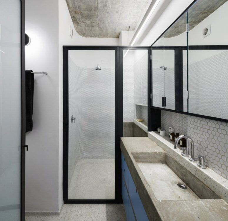 White penny tiles paired with concrete and sleek blue surfaces make the space bold