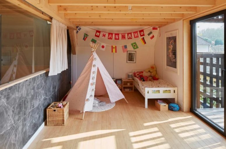 The kid's room features a bed, a teepee, some bold art and garlands and an entrance to the balcony