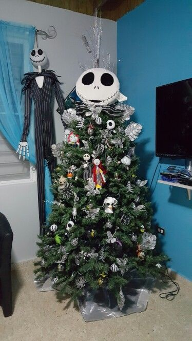 a Christmas tree decorated with Nightmare Before Christmas ornaments and with Jack Skellington standing next to it