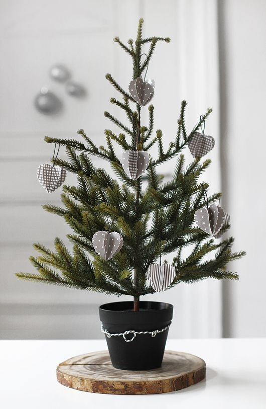 a Nordic tabletop Christmas tree in a pot decorated with grey and white 3D cardboard ornaments is a pretty and eco friendly idea