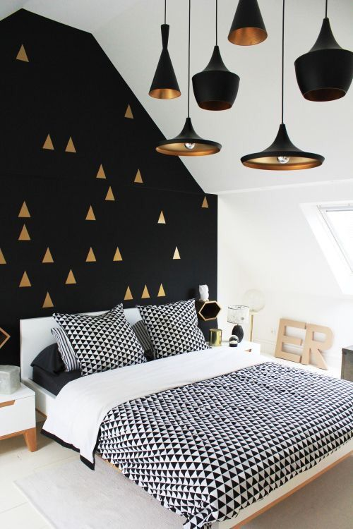 a Scandi space with a mid-century modern feel and a black wall with a gold triangle print