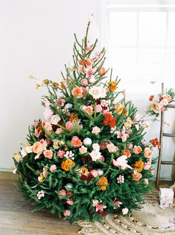 a beautiful Christmas tree with orange, rust, burgundy, blush and pink blooms, some branches and leaves is a very cute and romantic idea