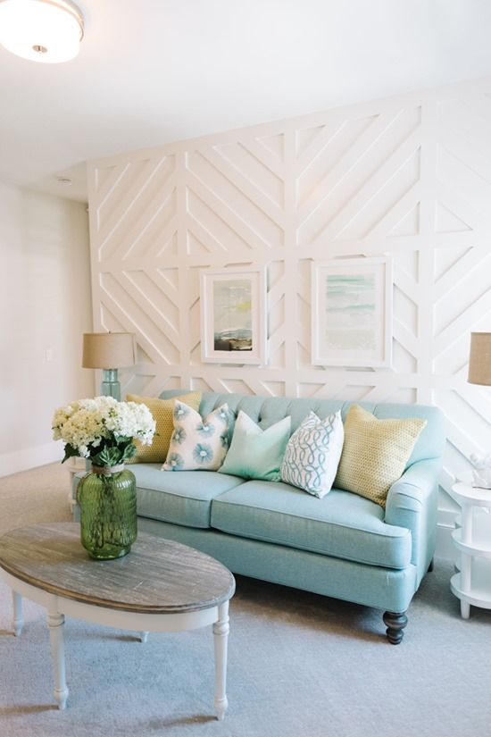 a beautiful coastal living room with a white geometric pattern wall, a blue sofa, white furniture, artworks and white blooms
