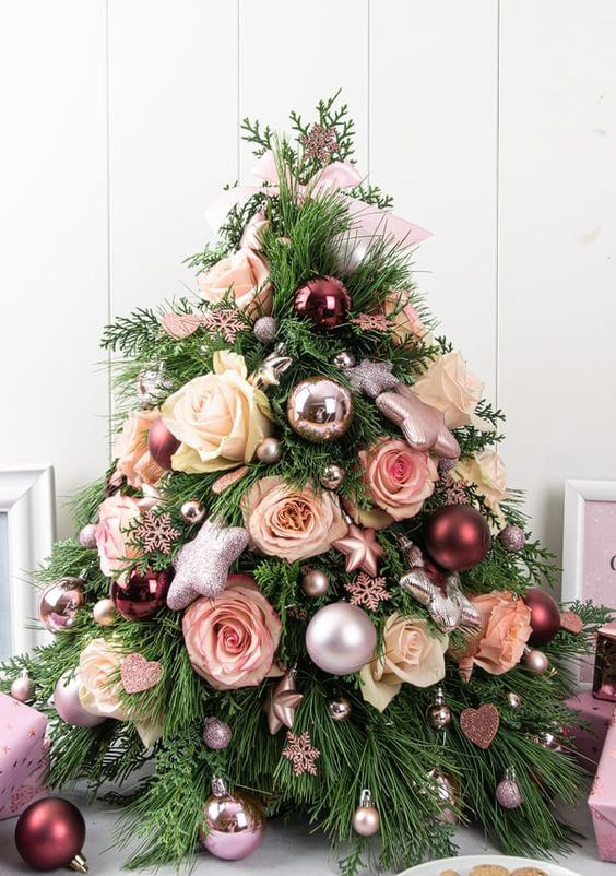 a beautiful glam Christmas tree decorated with shiny metallic ornaments, roses in white and blush, mini snowflakes and stars is a lovely idea