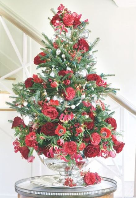 a beautiful tabletop Christmas tree with greenery, red and burgundy fresh flowers plus some silver ornaments is an elegant idea