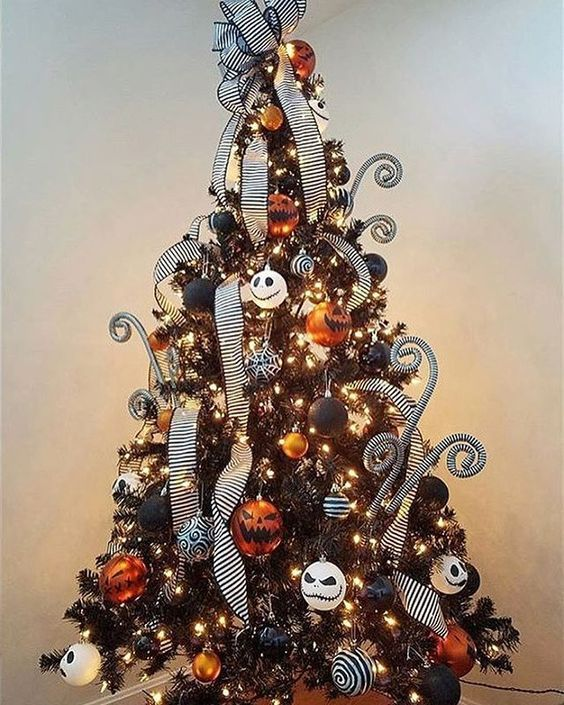 a black Christmas tree with lights, orange, black and white ornaments and Jack Skellington ones, striped ribbons and curls