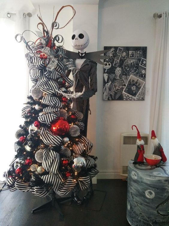 a black Christmas tree with striped ribbons, gold, silver, red and black ornaments and a Jack Skellington figure next to it