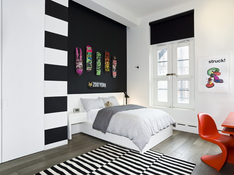 a black accent wall with colorful skates is a bold idea for a modern space, will fit a teenager room a lot