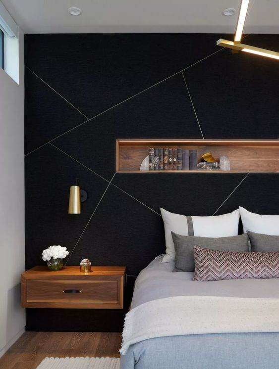 a black accent with gold geometric patterns and a wooden niche with books is a stylish idea for making a statement in a bedroom